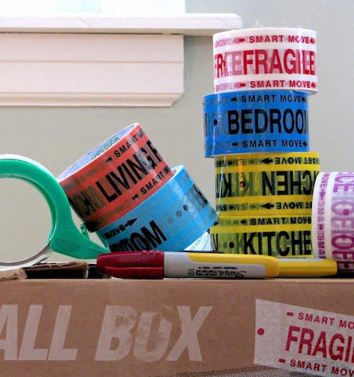 A moving box with rolls of packing tape and markers on it.