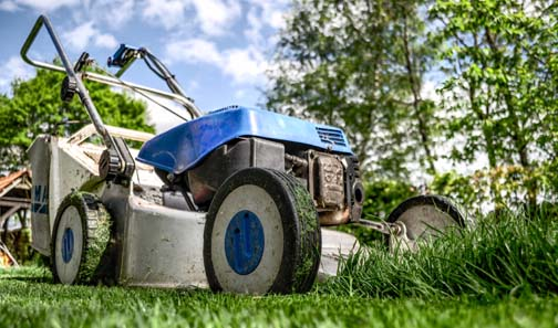 Lawn mower on green grass - a great summer job for teens.