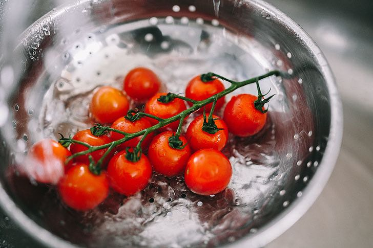 Tomatoes being rinsed in a collander.