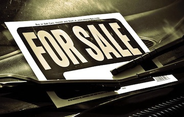 A for sale sign in the front window of a car.