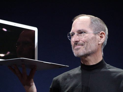Steve Jobs holding an apple macbook pro.
