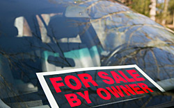 A for sale by owner sign sitting on the windshield of a car.