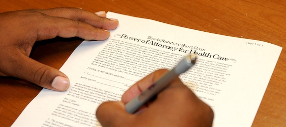 A power of attorney form for healthcare being signed.