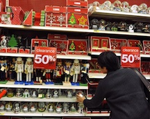 A male shopper looking at discounted Christmas sale items.