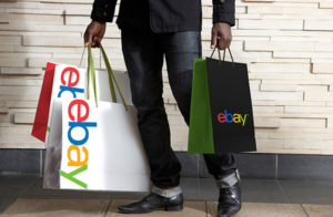 A person holding ebay shopping bags