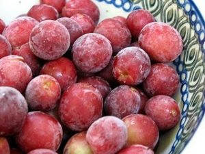Frozen red grapes in a bowl.