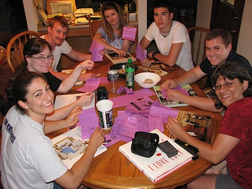 A group of people sitting around a table playing Telephone Pictionary Game