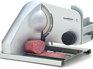 A silver meat slicer with a chunk of salami on it.