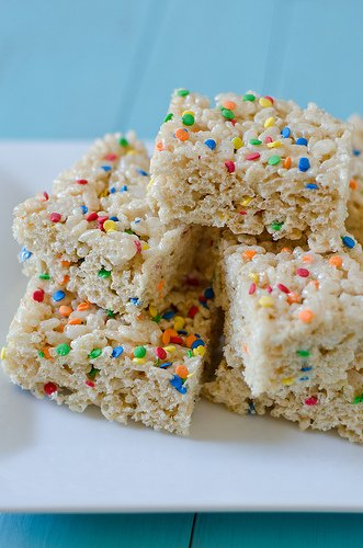 Rice Krispies Treats covered with sprinkles and full of colored cereal.