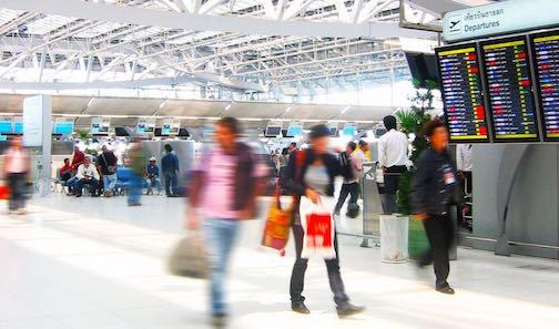 Travelers pulling luggage through an airport terminal.